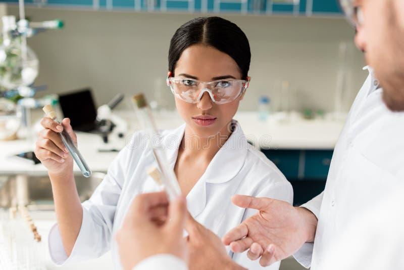 Scientifique féminin tenant le tube à essai avec du réactif et regardant l'appareil-photo dans le laboratoire photographie stock