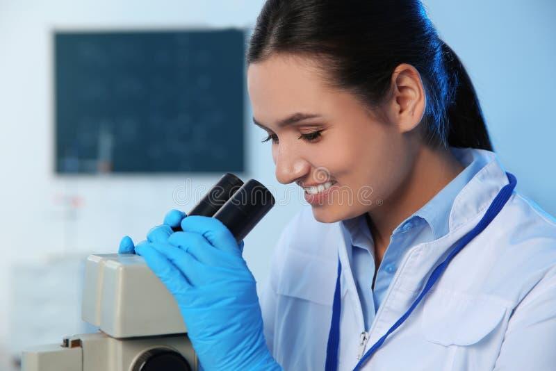 Scientifique f?minin ? l'aide du microscope dans le laboratoire de chimie photographie stock libre de droits