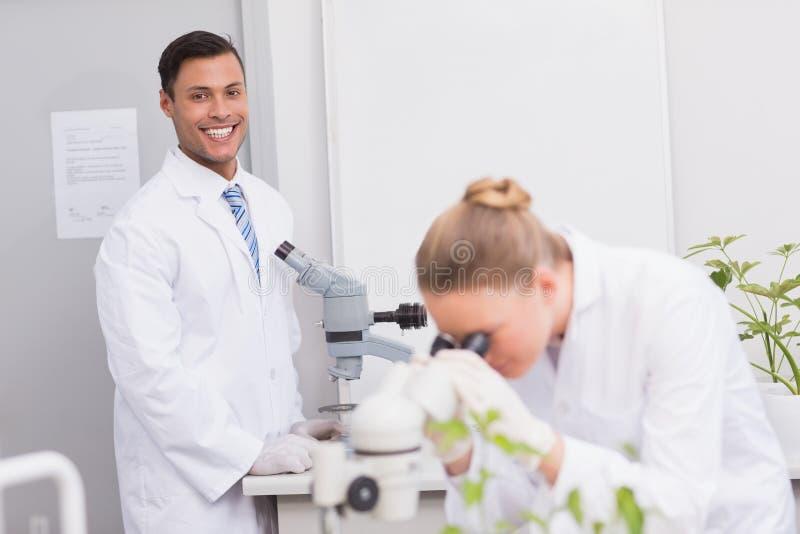 Scientifique heureux souriant à l'appareil-photo utilisant le microscope image libre de droits