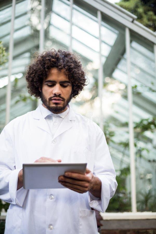 Scientifique masculin à l'aide de la tablette en dehors de la serre chaude photos libres de droits