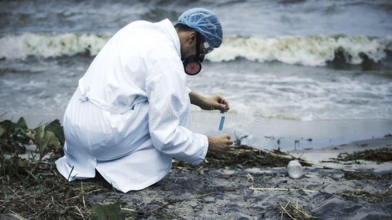 Scientifique réalisant l'essai toxique de pollution de lac, sources d'eau douce endommagées image stock