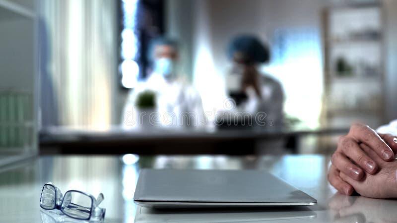 Scientifique s'asseyant à la table avec l'ordinateur portable fermé, travail fini sur le projet de recherche photos stock