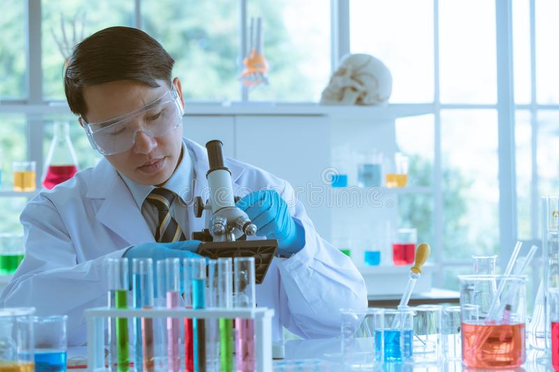 Scientist adjusting microscope for experiment stock images