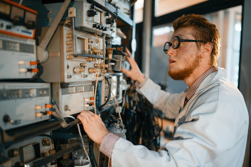 Scientist adjusts electrical device in laboratory royalty free stock image
