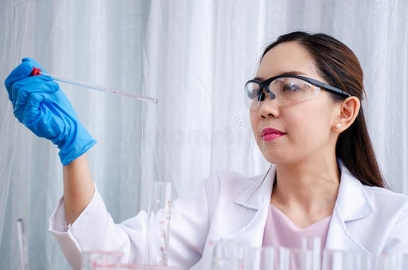Scientist beautiful woman research and drop medical chemicals sample in test tube at laboratory, Science, chemistry, technology, stock image