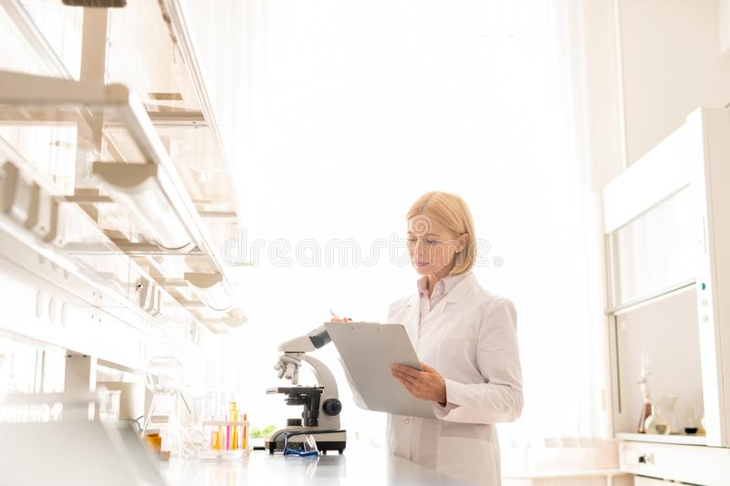 Scientist checking information before experiment. Serious busy mature female scientist in lab coat standing in laboratory room and checking information in royalty free stock images