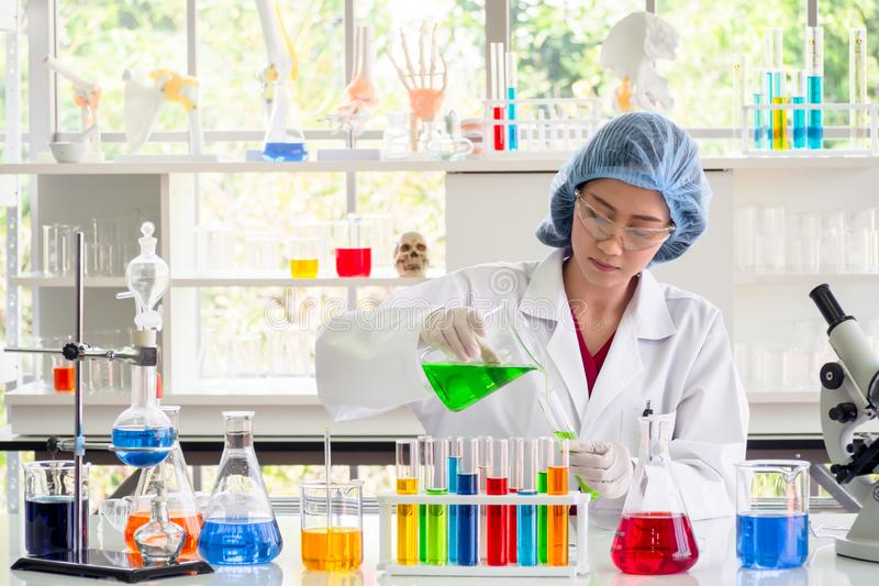 Scientist or chemist pouring green liquid substance into test tube royalty free stock photography