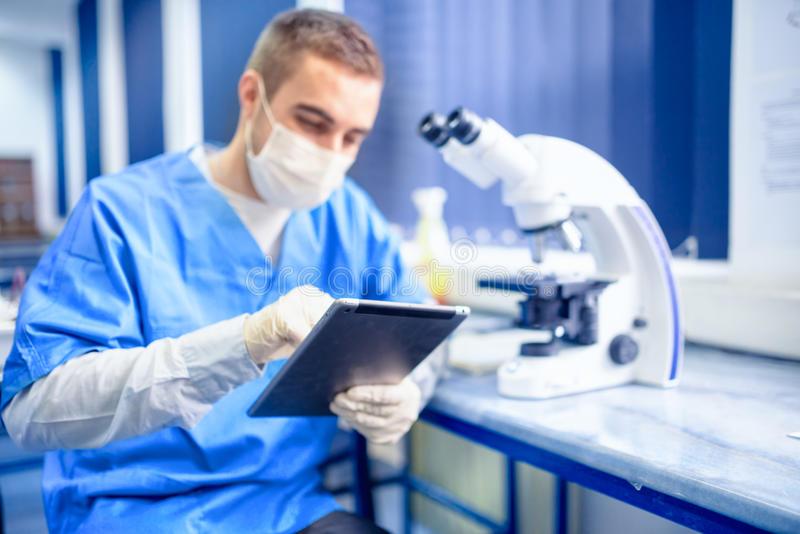 Scientist and chemist working with tablet and microscope at experiments royalty free stock images