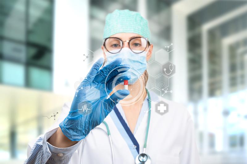Scientist doctor holding a red and white pill with futuristic virtual medical icons. Future illness cure. Medicine concept stock photos