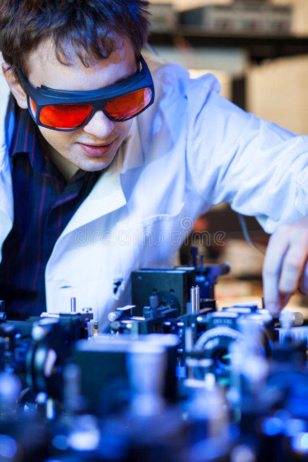 Scientist doing research in a quantum optics lab. (shallow DOF; color toned image royalty free stock photography