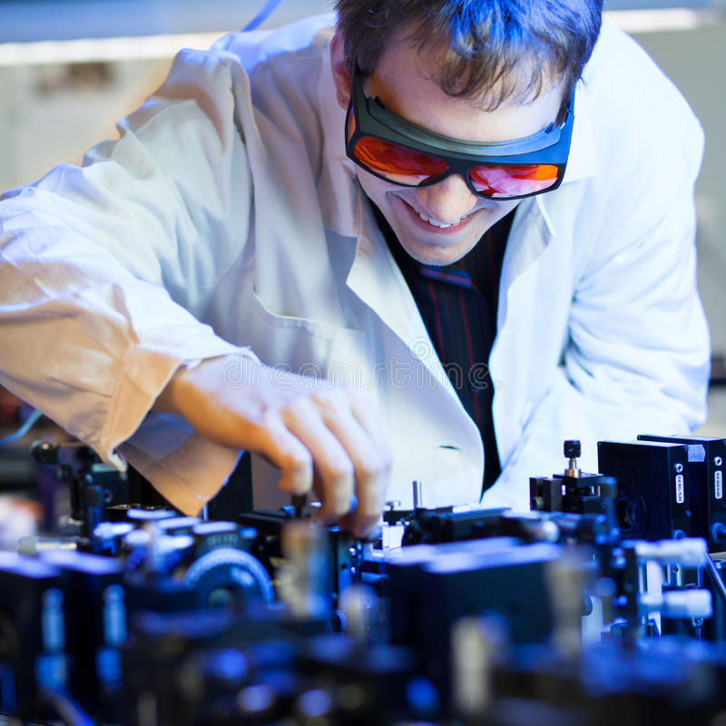 Scientist doing research in a quantum optics lab. (shallow DOF; color toned image stock photography