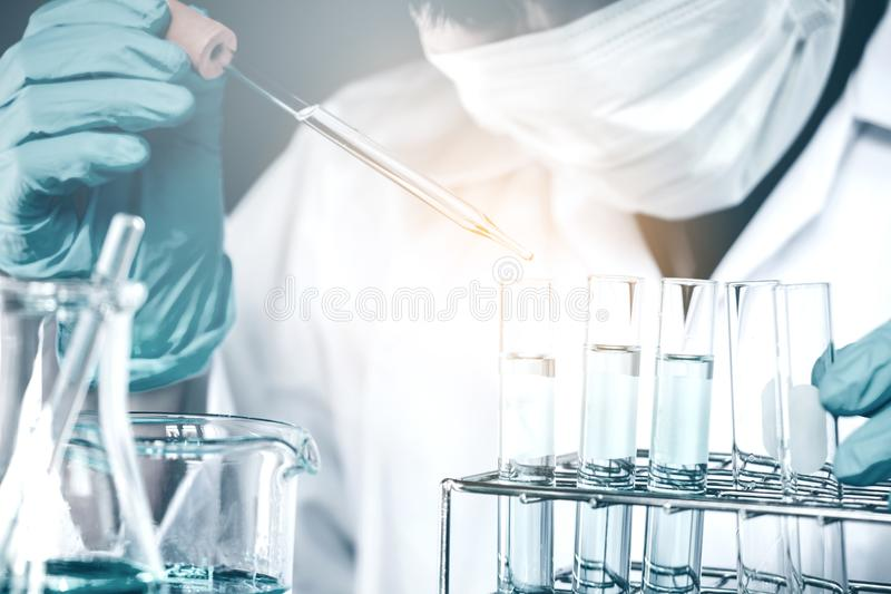 Scientist dropping chemical liquid to flask in lab Glass laborat stock photo