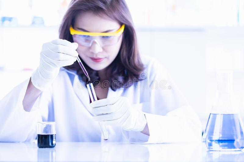 Scientist dropping purple liquid to test tube royalty free stock images