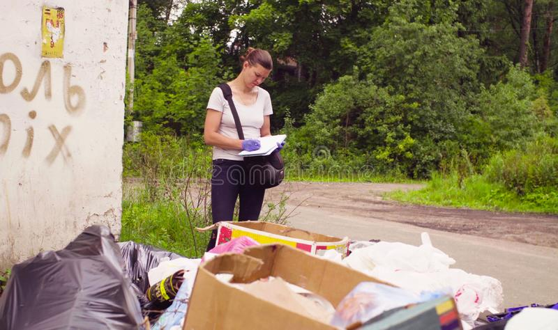 Scientist environmentalist near garbage dump making notes in the diary stock photos