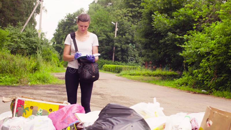 Scientist environmentalist near garbage dump making notes in the diary stock images