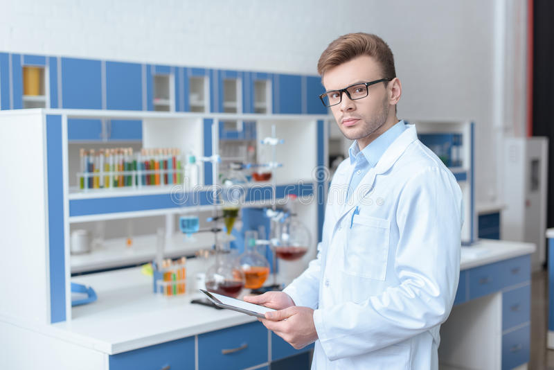 Scientist in eyeglasses and lab coat holding digital tablet. Young man scientist in eyeglasses and lab coat holding digital tablet and looking at camera royalty free stock photo