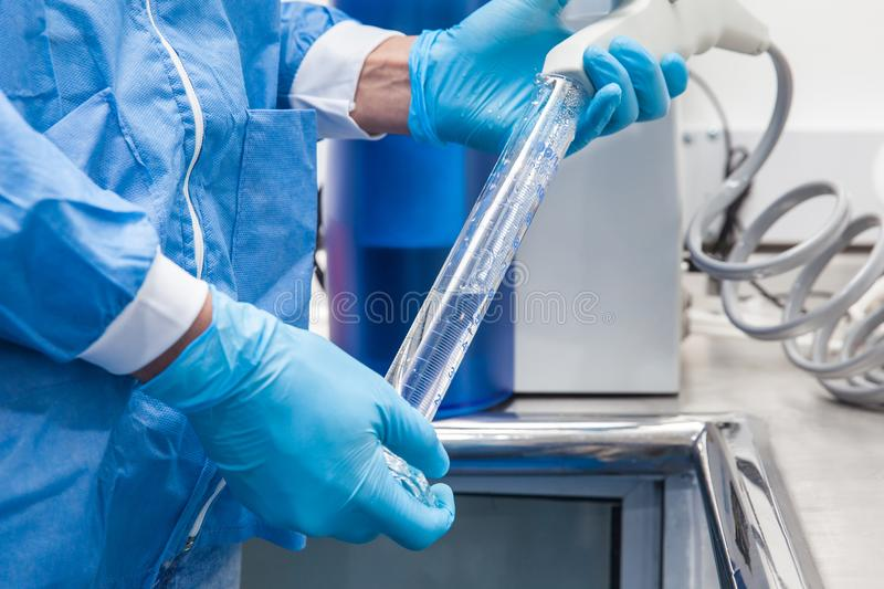 Filling a graduated cylinder with distilled water at laboratory royalty free stock photos