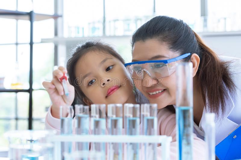 Scientist girl and teacher dropping solution substance liquid with pipette into test tube in lab classroom together. Education and stock photos