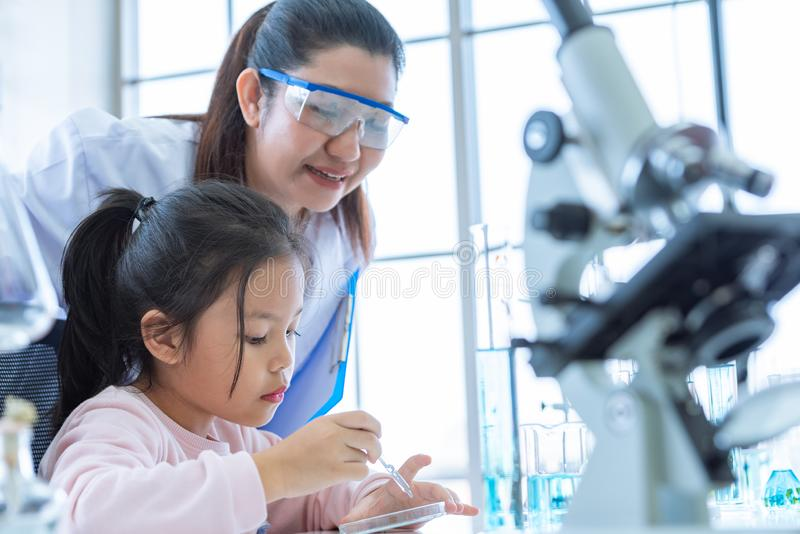 Scientist girl and teacher dropping solution substance liquid with pipette into test tube in lab classroom together. Education and stock images