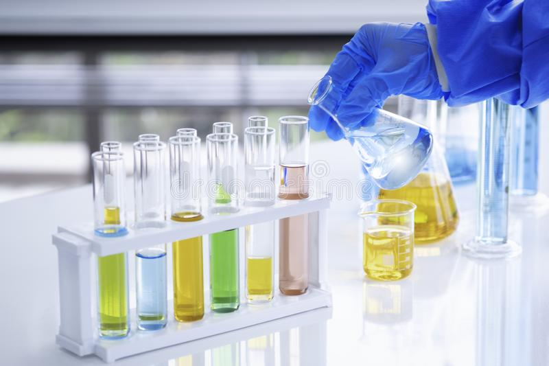 The scientist is hand holds a beaker of chemicals in the lab to prepare specimens to test royalty free stock images