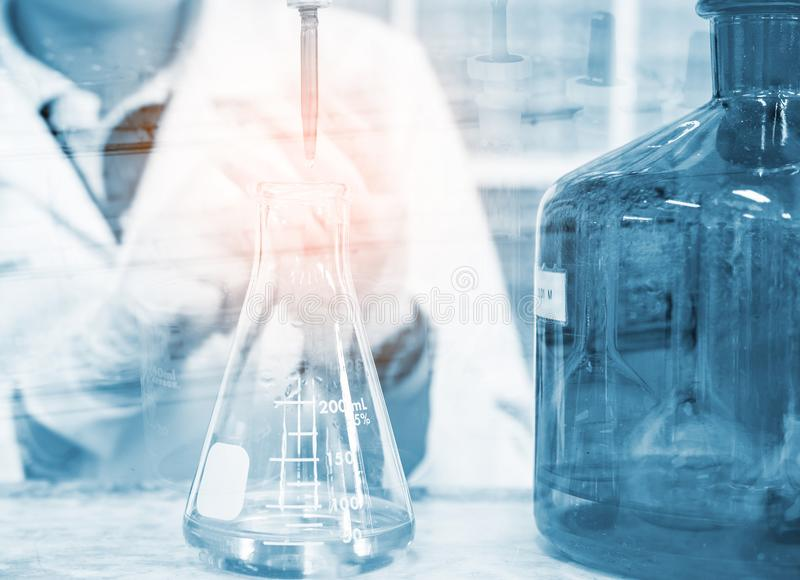 Scientist hand titration with burette and erlenmeyer flask, science laboratory research and development concept.  royalty free stock image