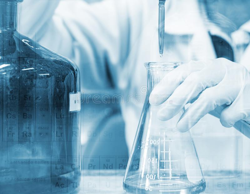 Scientist hand titration with burette and erlenmeyer flask, science laboratory research and development concept.  stock photo