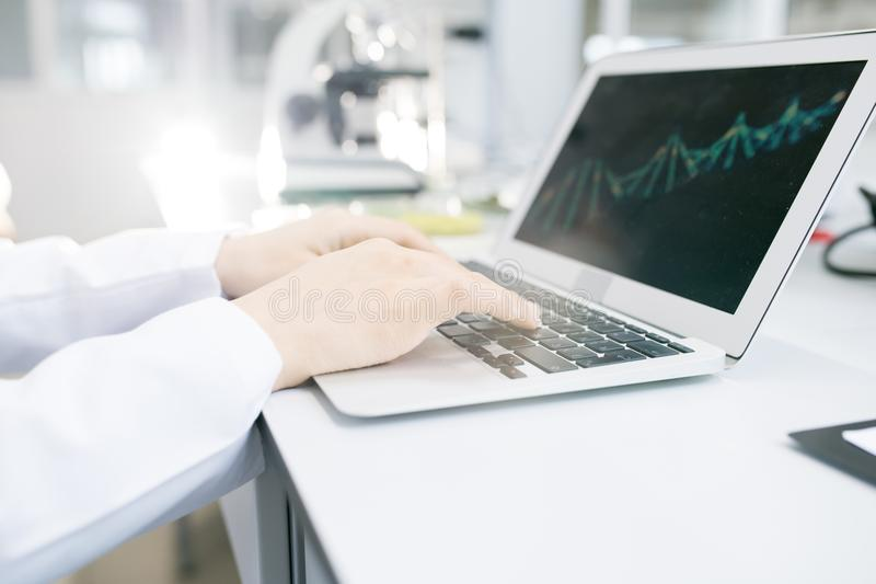 Scientist hands editing DNA model on laptop stock image