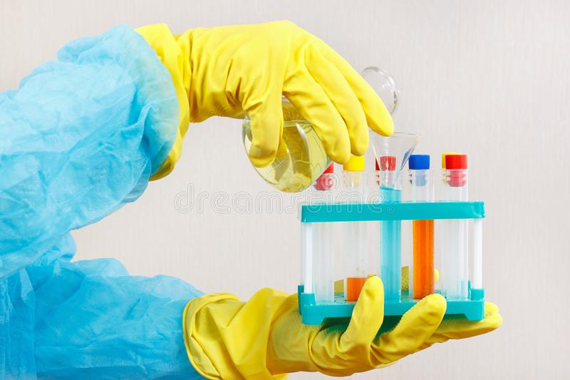 Scientist hands in rubber gloves doing chemical experiments in laboratory. Scientist hands in rubber gloves doing chemical experiments in the laboratory stock photography