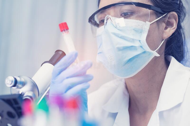 Scientist holding and analysis tube of micro biological sample with a microscope. In laboratory for doctor in the world stock image
