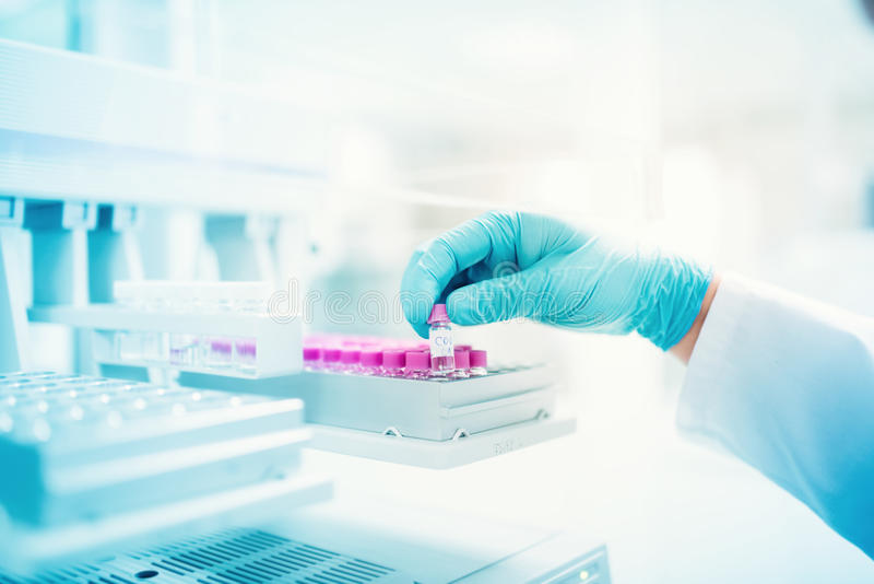 Scientist holding sample of experiment in pharmaceutical environment. close up of medical details royalty free stock photo