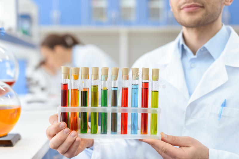 Scientist holding test tubes with reagents in lab. Close-up partial view of scientist holding test tubes with reagents in lab stock image