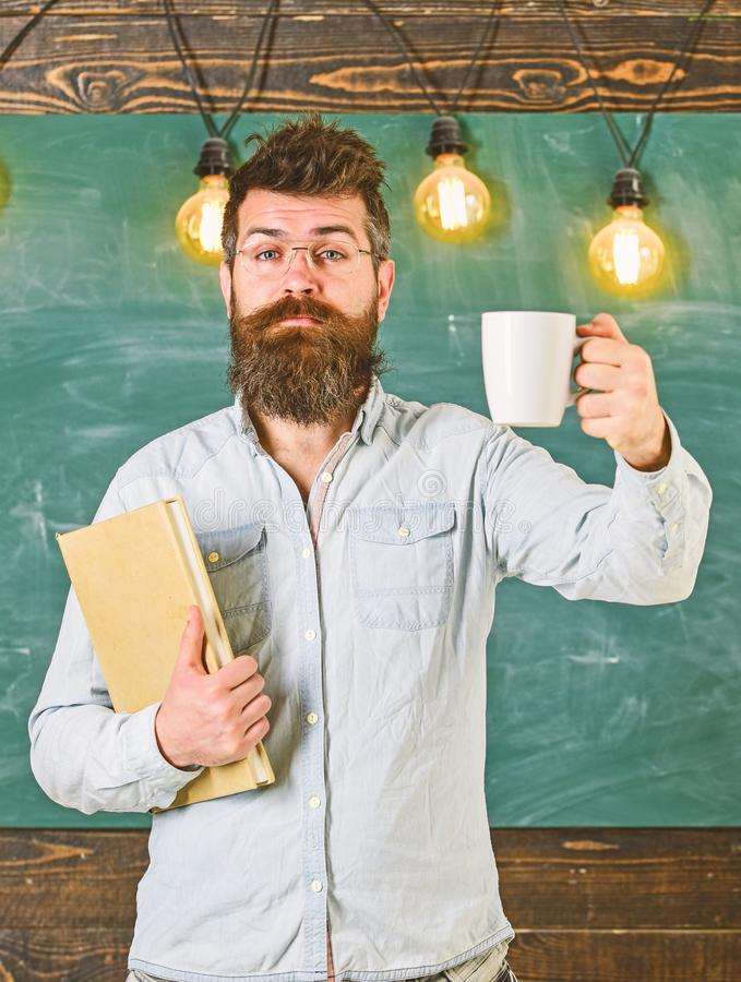 Scientist holds book and drinks coffee, chalkboard on background, copy space. Coffee break concept. Man with beard on royalty free stock images