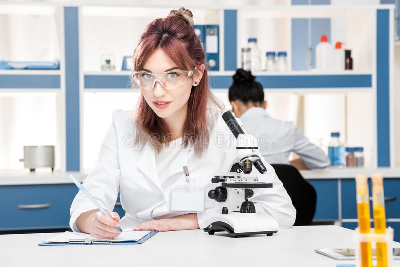 Scientist in lab coat working with microscope and writing in folder in chemical lab. Young scientist in lab coat working with microscope and writing in folder in royalty free stock images