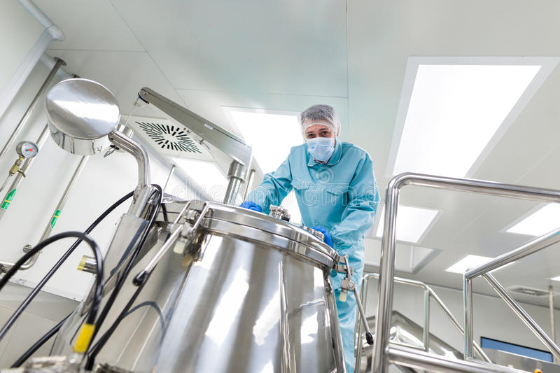 Scientist look in steel tank in laboratory. Caucasian scientist in blue lab suit and gloves stand on platform and look in the steel barrel, look at camera stock photo
