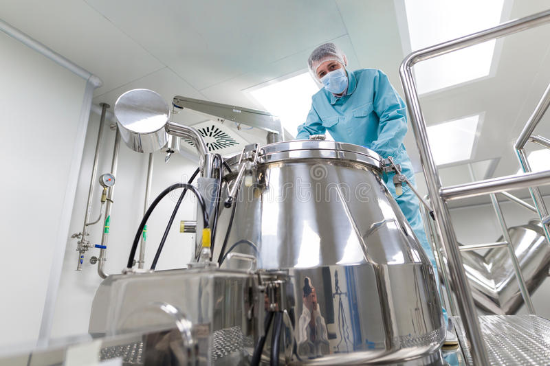 Scientist look in steel tank in laboratory. Caucasian scientist in blue lab suit and gloves stand on platform and look in the chromed barrel, look at camera royalty free stock images