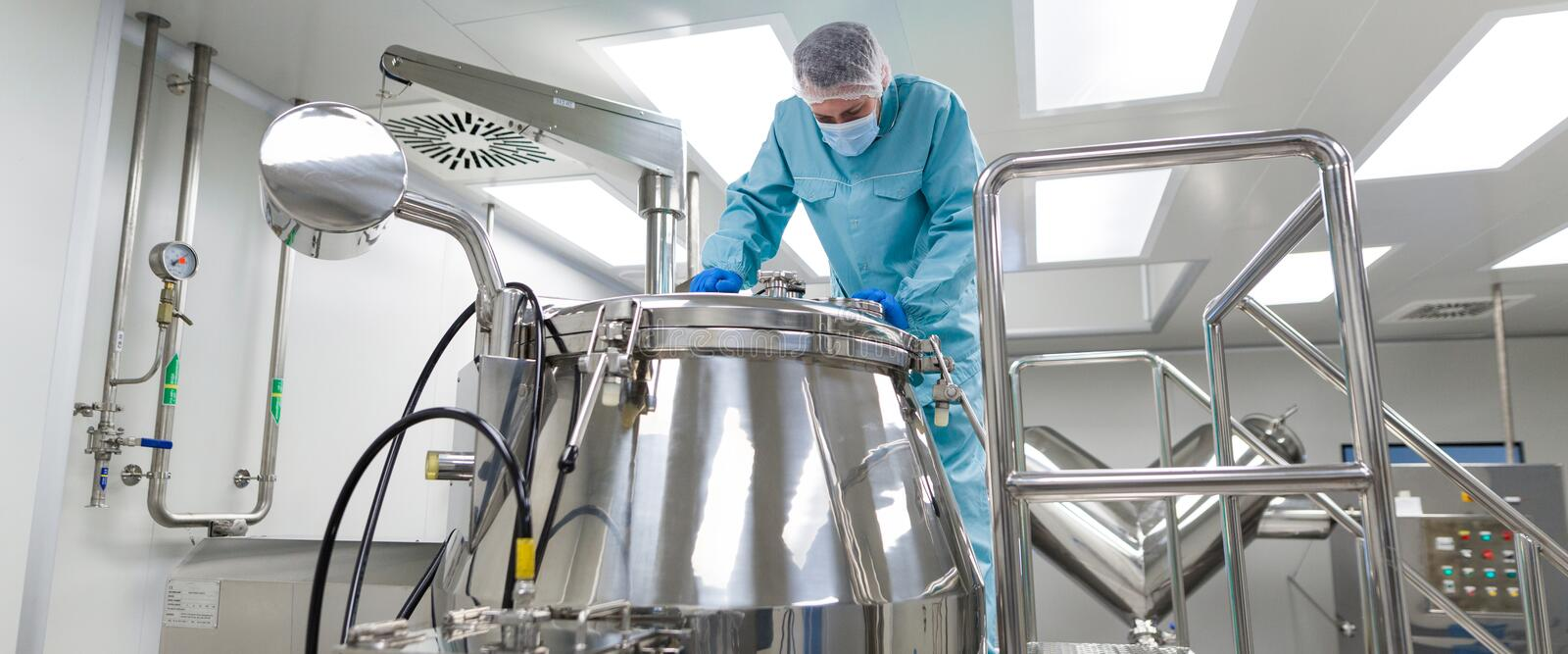 Scientist look in steel tank in laboratory. Widescreen picture, caucasian scientist in blue lab suit and gloves stand on platform and look in the steel barrel royalty free stock photography