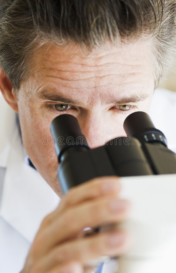 Scientist Looking Through Microscope Royalty Free Stock Photos