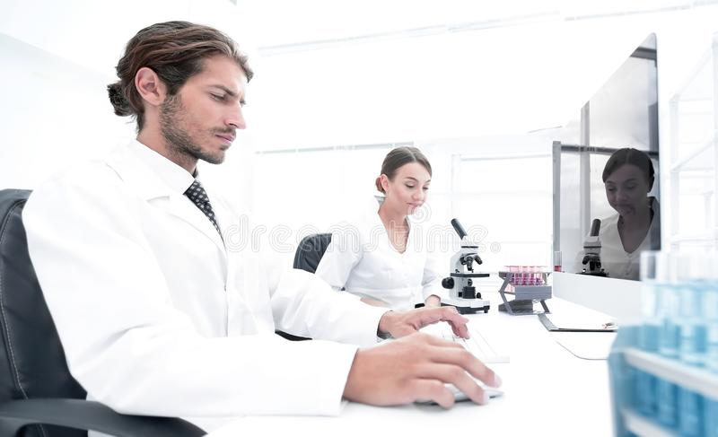 Scientist looking at specimen while his assistant helping him. Side view of a male scientist looking at the monitor, while his female colleague conducting an royalty free stock image