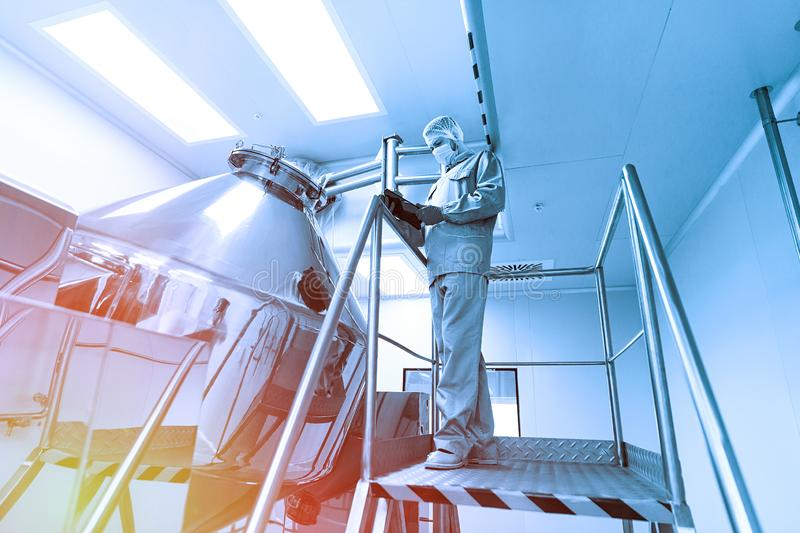 Scientist make notes about big metal tank. Blue tone. Blue tint. Caucasian scientist in blue lab suit and gloves stand on steel ladder and make notes about royalty free stock image