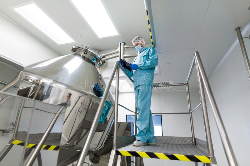 Scientist make notes about big metal tank. Caucasian scientist in blue lab suit and gloves stand on steel ladder and make notes about chromed tank stock images