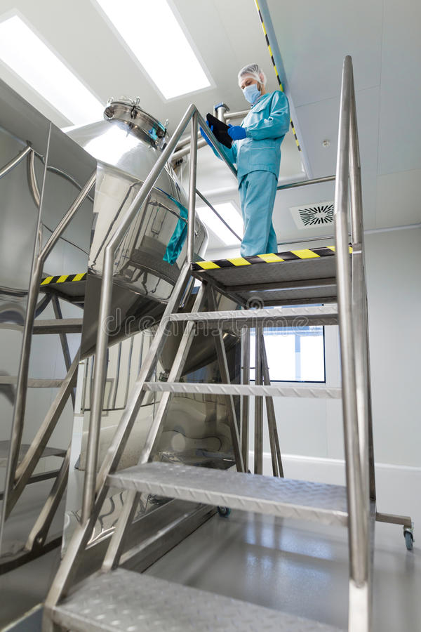 Scientist make notes about big metal tank. Vertical picture, caucasian scientist in blue lab suit and gloves stand on steel ladder and make notes about chromed royalty free stock image