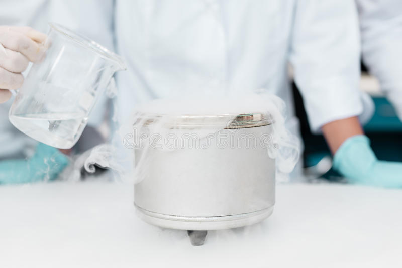 Scientist making experiment with dry ice in chemical laboratory. Close-up partial view of scientist making experiment with dry ice in chemical laboratory royalty free stock image