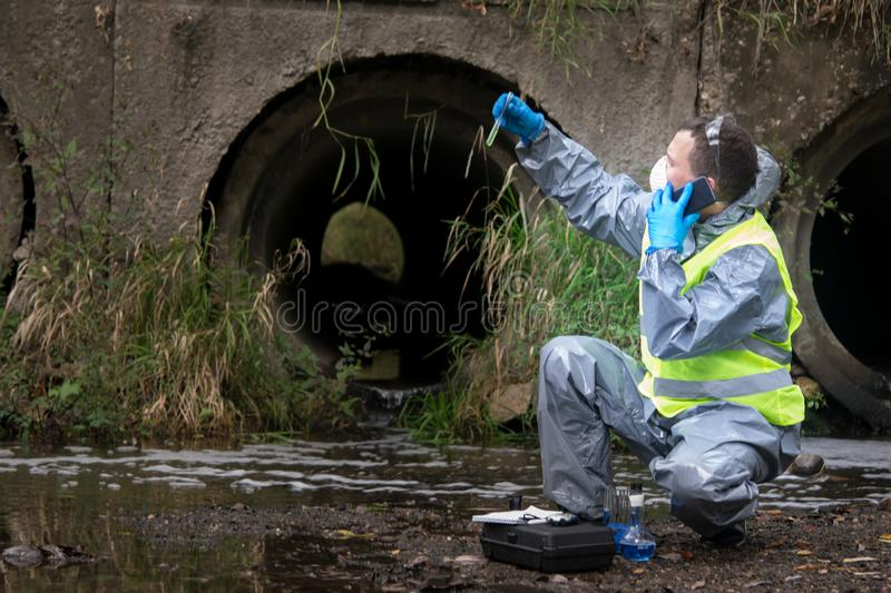 Scientist in protective suit, gloves and mask, holding a vial of liquid and is calling on mobile phone user to report results of stock photo