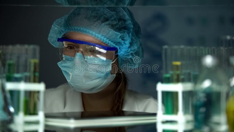 Scientist in protective uniform looking at samples in tubes, chemical industry stock photography