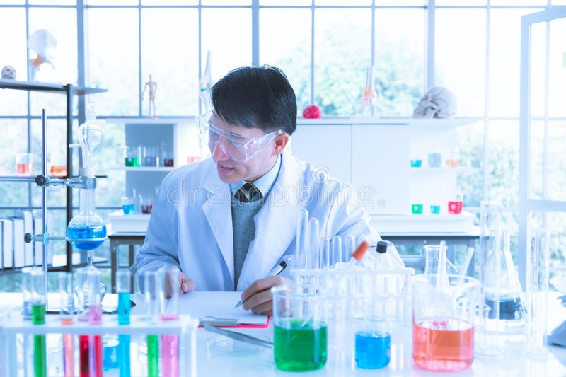 Scientist recording experiment result in lab room stock photography