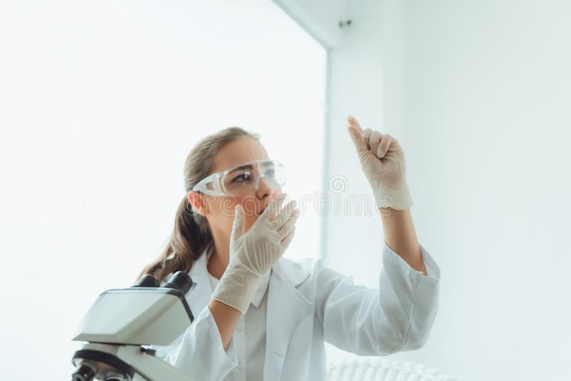 Scientist research laboratory in secure glasses using microscope for analyzing anti bacteria through slide glass, Technology of stock image