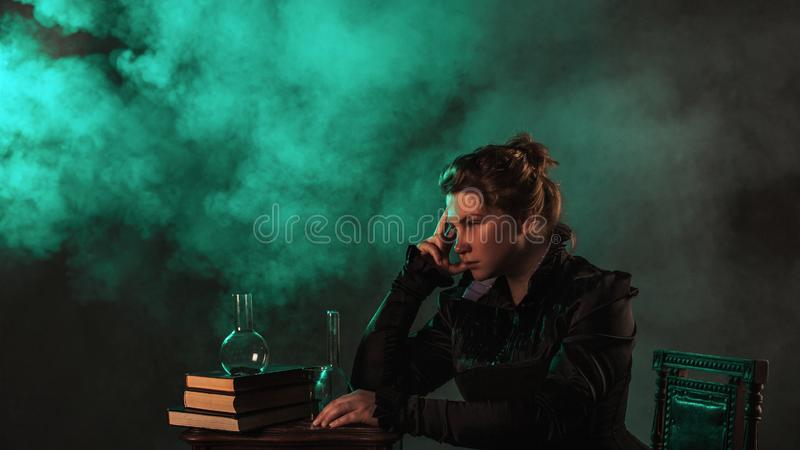 Scientist researcher on abstract background. History of science, great physical discoveries, structure of atom. Image in style of Marie Curie, concept royalty free stock photography