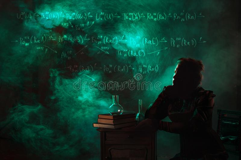 Scientist researcher on abstract background of schemes and formulas. History of science, great physical discoveries. Radioactivity and structure of atom. Image stock image