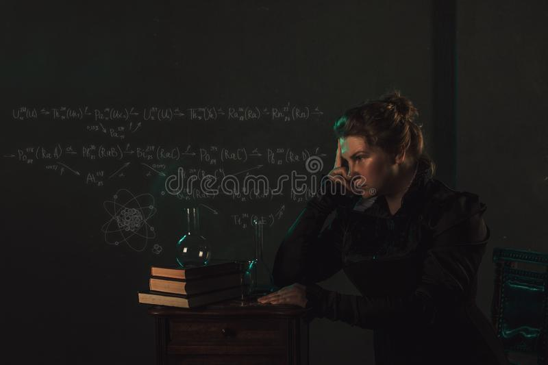 Scientist researcher on abstract background of schemes and formulas. History of science, great physical discoveries. Radioactivity and structure of atom. Image stock photography