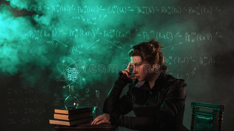 Scientist researcher on abstract background of schemes and formulas. History of science, great physical discoveries. Radioactivity and structure of atom. Image royalty free stock photo